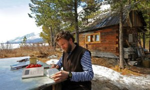 Sylvain Tesson reading outside his cabin