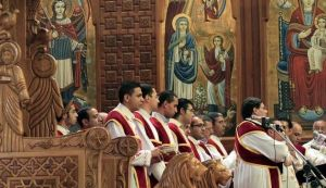 Members of the Egyptian Coptic Choir stand near the chair of the late Pope Shenouda during mass at Abassaiya cathedral in Cairo