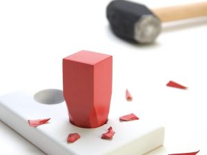 A square red peg hammered into a round hole surrounded by small pieces of the peg. Hammer in the background. On a white background